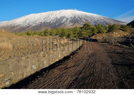curve dirt track to the volcano Etna snow covered, Sicily