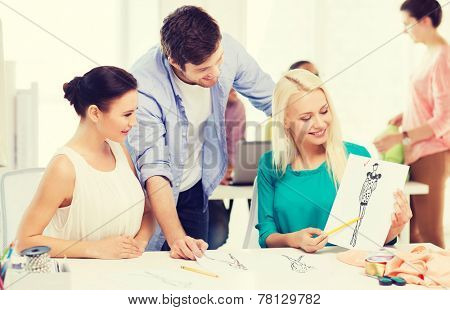 startup, education, fashion and office concept - smiling fashion designers working in office