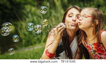 Family happiness and carefree concept. Mother and daughter little girl having fun blowing soap bubbles together in park green blurred background poster