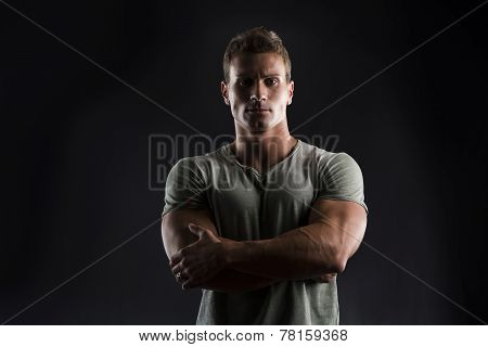 Handsome Muscular Fit Young Man On Dark Background With Stern Expression