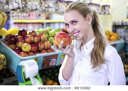 Woman Smelling A Mango In The Supermarket