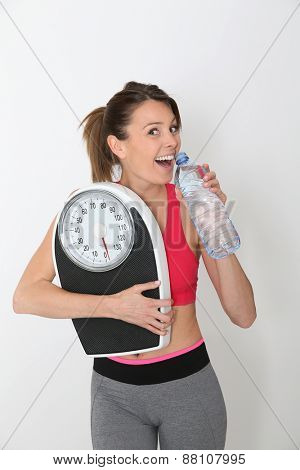 Cheerful fitness girl with bottle of water, holding scale, isolated