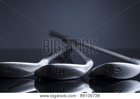 Golf clubs lying on reflective surface, isolated on dark blue background with empty copy space for text.
