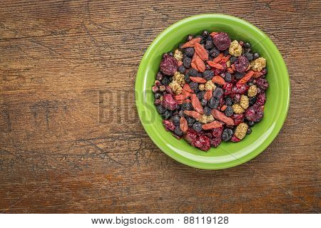 superfruit berry mix (blueberry, mulberry, cherry, goji, elderberry, chokeberry, and cranberry) - green ceramic bowl against grunge wood