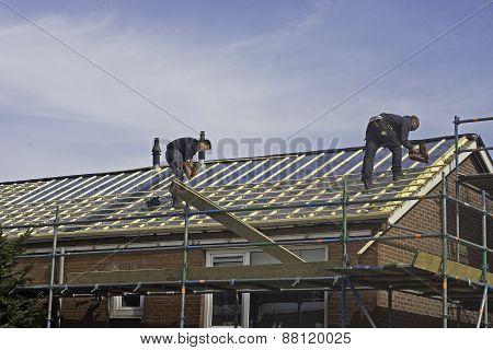 Carpenters applying roof battens