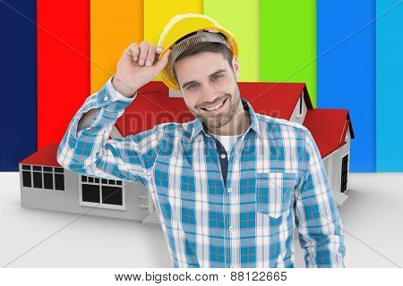 Confident male technicial wearing hard hat against digitally generated house poster