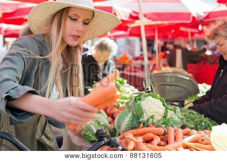 Attractive blonde girl with straw hat buying vegetables on  marketplace. poster