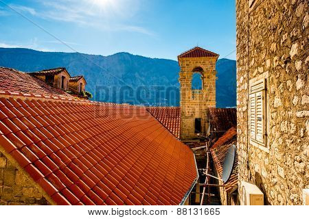 Top view with tiled red roofs and mountains in Kotor old city in Montenegro poster