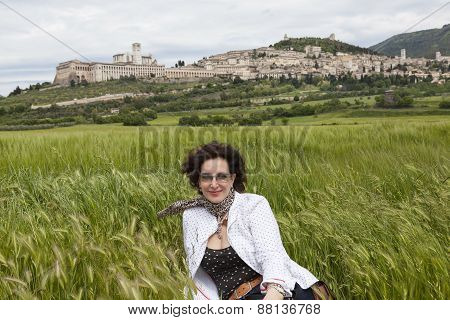 A woman sitting in a field of wheat at the foot of InGen. Gubbio. Umbria. Italy