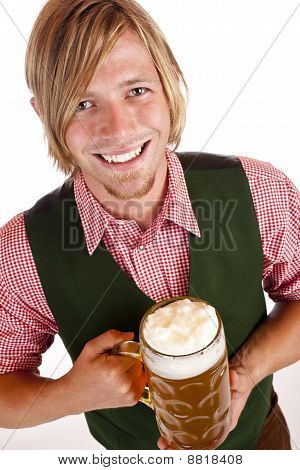 Mman holds oktoberfest beer stein and looks happy into camera.