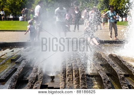 People Having Fun With Water In The Fountain