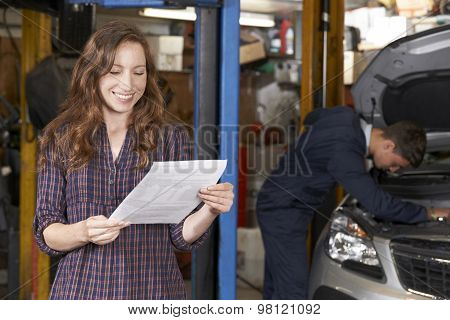 Female Customer In Auto Repair Shop Satisfied With Bill For Car Repair