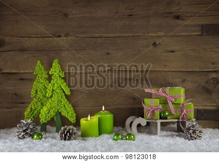 Two apple green burning candle lights for advent. Christmas decoration with gifts on wooden old brown country background.