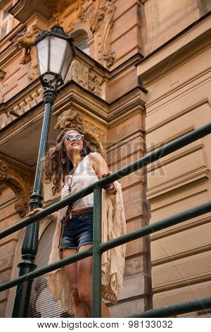 Hippy Girl With Sunglasses Stands Near Old Town Stree