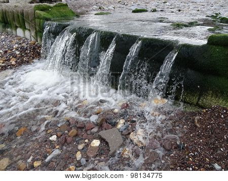 River Waterfall Upon Beach