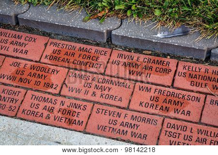 SEDALIA, MO, USA - AUGUST 3, 2015: Engraved veteran memory bricks in sidewalk pavement surrounding Pettis County Courthouse in historic downtown of Sedalia. Missouri.