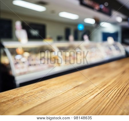 Table Top Counter With Blurred Fresh Food Butcher Display In Supermarket
