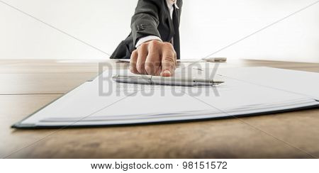 Front view of a businessman offering you to sign a document or contract on a wooden desk. Focus to the fountain pen. poster
