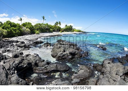A beautiful black and white gravel beach with clear blue water on a remote beach in Kona Hawaii.