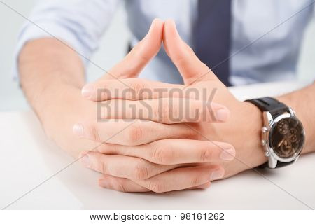 Hands of man lying on the table
