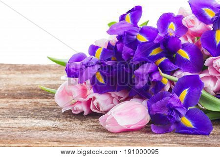 Blue irises and pik tulips on wooden aged background with copy space