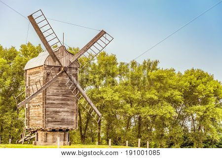 Wooden windmill on a background of green trees. Summer landscape.