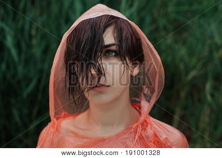 The portrait of girl in red raincoat under the rain. Sad and serious emotion on her face. She is upset because of the rain Close up.