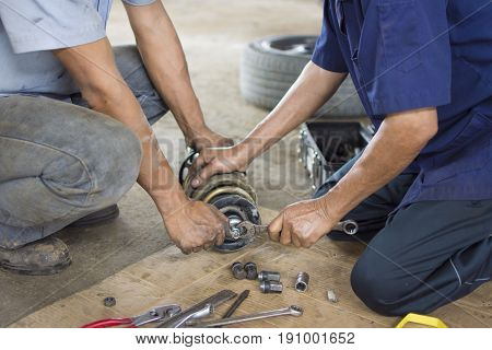 Repairing a car suspension. fixing a car shock absorber in auto mechanic shop.
