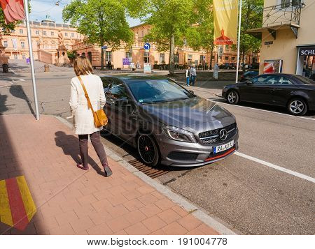 RASTATT GERMANY - APR 13 2017: German woman walking near the new generation of the Mercedes-Benz A-Class near the Schloss Rastatt Castle. Mercedes A-Class reconciles the conflicting aims of sportiness and comfort.