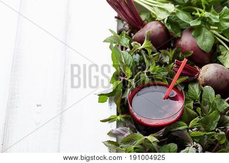 Fresh beetroot juice with herbs in white wooden tray, copy space