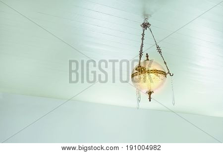Antique brass lamp with beautiful appearance on the ceiling of the blue house.