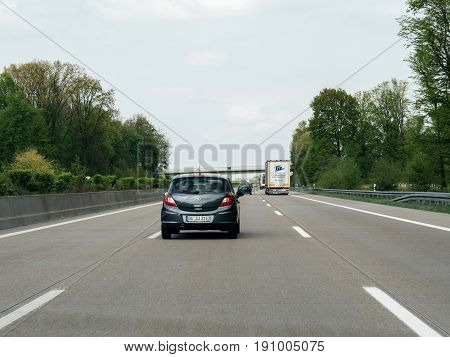 FRANKFURT GERMANY - APR 13 2017: Driver point of view pov of black Opel Corsa driving on German Autobahn Bundesautobahn or Federal Motorway highway with speed limits of 100 kmh electronic street sign