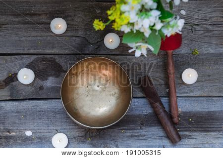 Tibetan singing bowl and special sticks burning candles and vase with flowers on the dark wooden background top view. Selective focus.