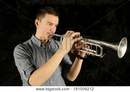 Portrait of trumpet player in a gray shirt in a black room