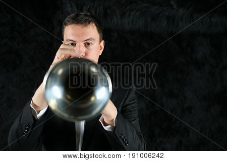 The musician blows into the trumpet on a black fur ground