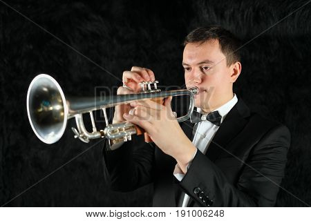 Portrait of trumpet player on a black fur ground