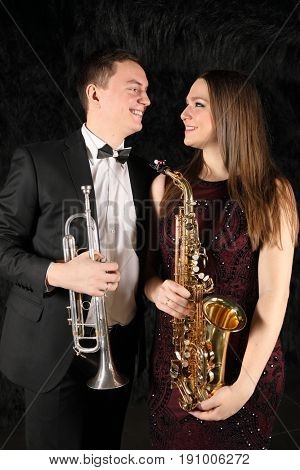 Happy musicians with wind instruments in their hands on a black fur ground