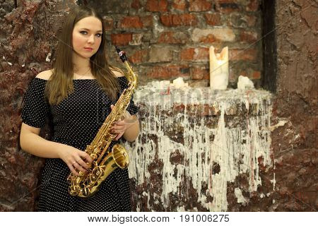 Portrait of a young woman with saxophone in front a brick wall with a candle and a wax coating