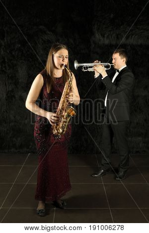 Woman with long hair playing on saxophone in front of a man with trumpet in a black room