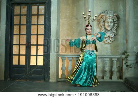 Beautiful woman in a green dress decorated with pearls and chandelier on her head performs Arabic dance