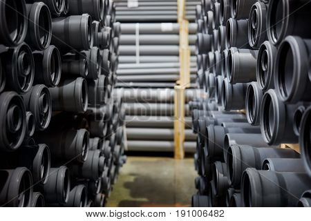 Plenty of gray plastic pipes at indoor storage, shallow dof.