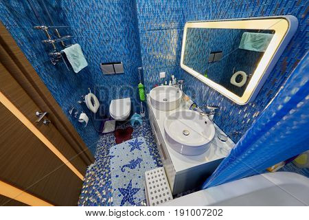 Bathroom in blue tones with shower basins, toilet bowl, child potty, litterbox. Walls and floor covered with ceramic tiles.