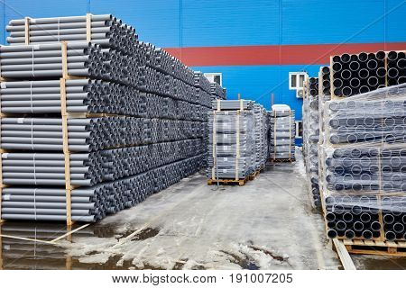Plenty of grey plastic water pipes at outdoor storage.