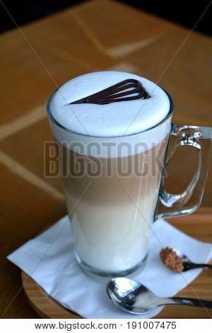 Foamy Latte Macchiato On Glass Cup On A Wooden Table
