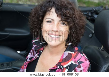 Smiling Woman Forties In Convertible Car In Summer Day