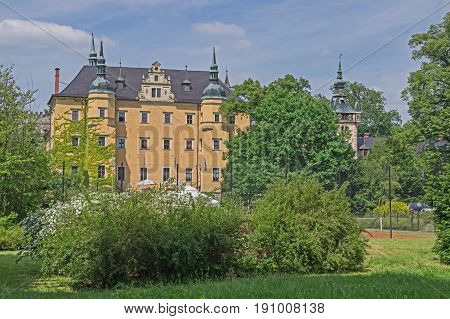 The photograph shows the historic put castle in the town Kliczków in południowo - for western Poland. The facade of the castle is painted of yellow colour. He has two round towers. The copper roof is covered with the patina giving a green colour him. Arou