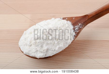 Spoon of corn starch on wooden background