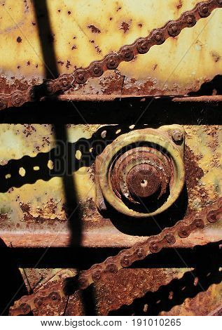Chains casting shadows on old rusting farm equipment in Texas
