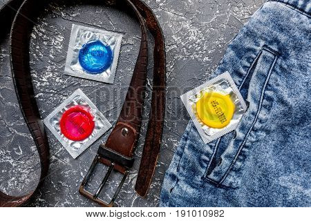 male contraception with condom in jeans on dark table background top view