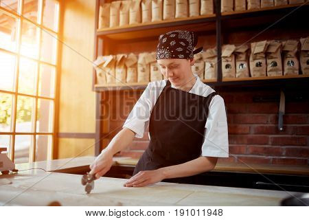Female cook in apron slicing a knead for pasta on cafekitchen. Woman slicing pasta in restaurant. Making pasta. Making pasta in restaurant.